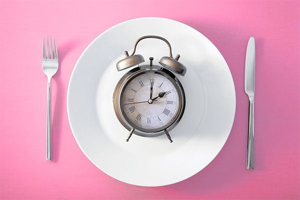 concept of intermittent fasting - a clock on a plate